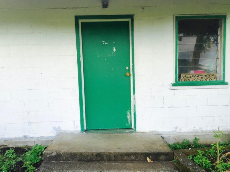 The plain, green front door of the clinic